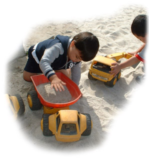 Children playing with trucks in the sand