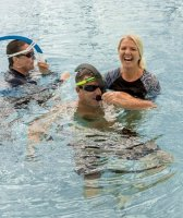 instructor with two students with snorkles