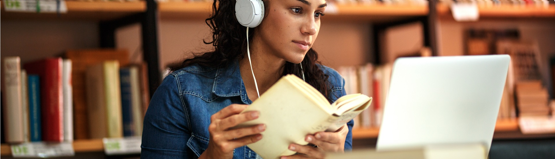 Woman with headphones with book and laptop