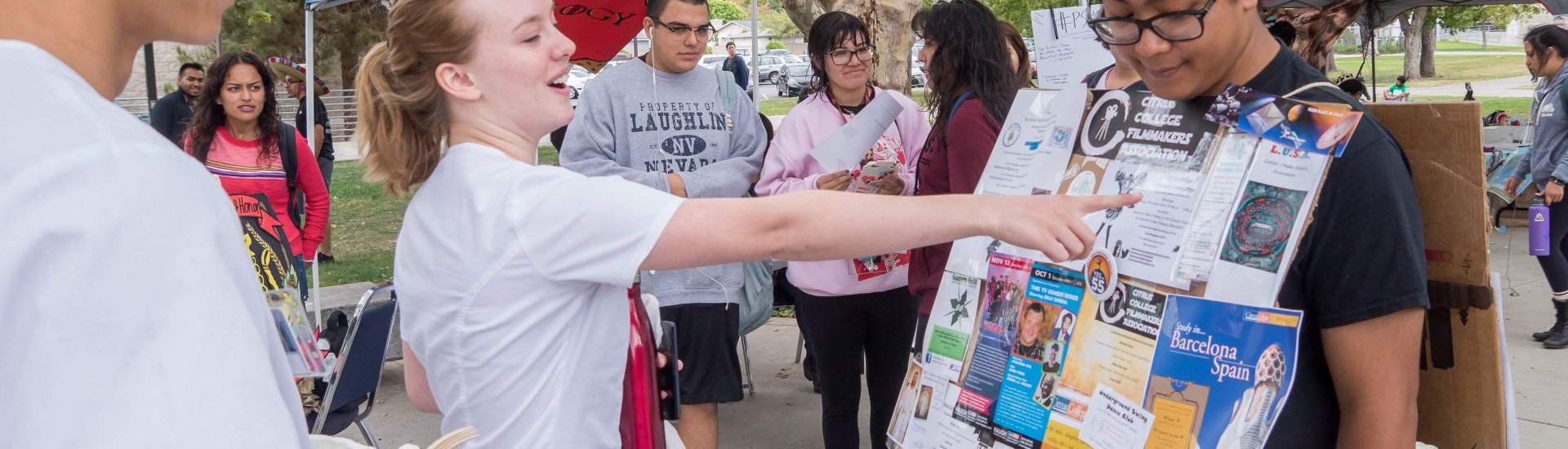 "student looking at ""walking billboard"" advertising available clubs during Club Rush"